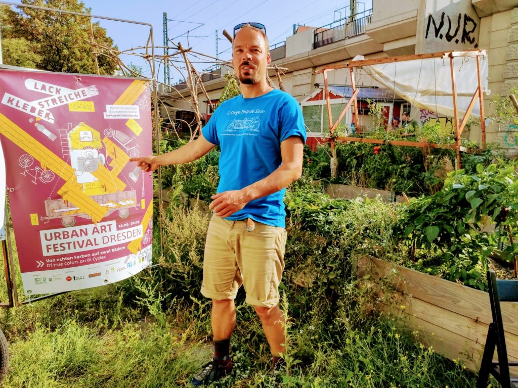 Urban-Art-Festivalorganisator Jens Besser bei der mobilen Lack StreicheKleber -Austellung im Gemeinschaftsgarten Hechtguen. Foto: Jenz Steiner